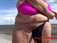 Huge mom and son napile behind shoting video at the beach changing bikinis