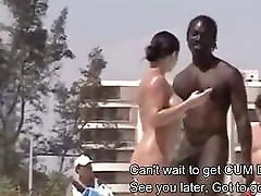 Nudist woman picking up Black man on beach