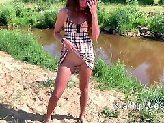 Cute girl sunbathes on a nudist beach and pisses in public
