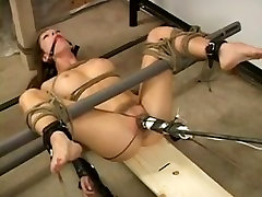 Young girl tied with a sex toy between her legs.