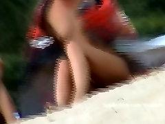 בחורה ערומה פותחת את הרגליים בחוף הים