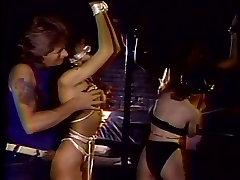Lesbians bound by a strip pole
