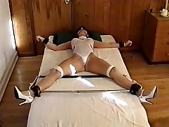Hottie with sexy tits, bound to the bed while her tits are teased