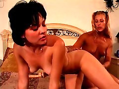 Hot young lesbians play with each other, a big dildo on the bed