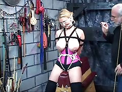 Cute blonde slave in corset with giant tits gets blindfolded in sex basement