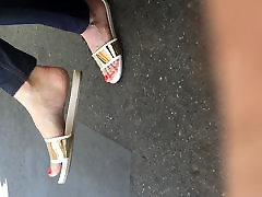 Sexy feet at London tube station, red toes dangling feet