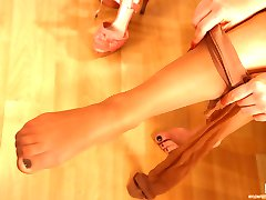 Lovely girl fondles her sexy feet thru pantyhose before wearing high heels