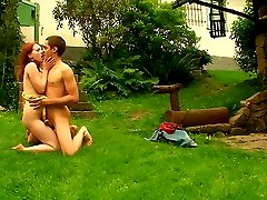 Out in the backyard, this redhead nympho lets her lover explore all of her body. He uses his...