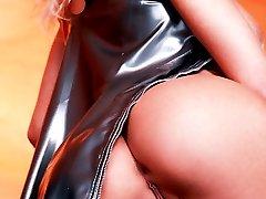 busty European blonde pulls up shiny latex dress
