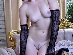Classy seductress smoothens fine hosiery on her legs with her gloved mitts