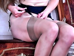 Willowy nude babe puts on sheer stockings with a black garter belt to work