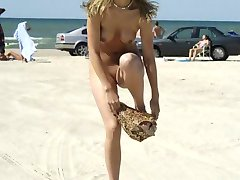 Wild blonde chick strips naked at a beach