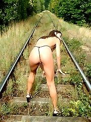 Horny brunette finger-fucking her slit on the train rails!
