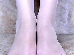 Frisky girl unbuckles her strappy sandals to flash her slender nyloned soles