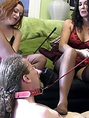 Mistresses trample and smother sissy slave with their high stilettos and nylon soles, as they use him as a submissive foot tabouret