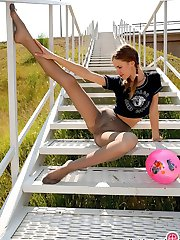 Pig-tailed chick in grey pantyhose playing hot games with a ball outdoors
