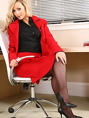 Sexy Alana wearing a red skirt suit and black blouse underneath.