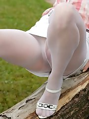 Brazen girl climbing a tree in her sheer white hose revealing her pink slit