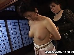 Mature whore gets trussed up and hung in a bdsm session