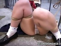 She is tied up to the prison cell and toy fucked
