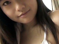 Грудастая Японская красотка демонстрирует свои прелести в белом бикини