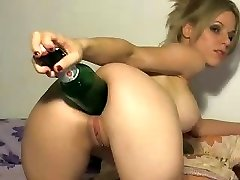 Crazy blonde uses the big end of a bottle to stick in her bum