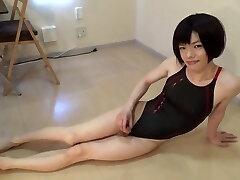 Crossdresser in a ebony swimsuit sitting and lying