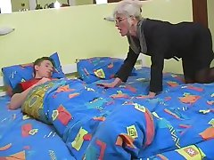 Mature with Silver Hair Glasses and Stockings Wakes the Boy