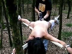 Trussed to a cross and fucked with a big dildo in the forest