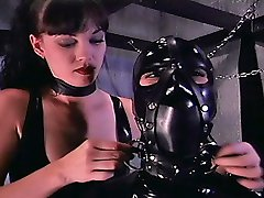 Brunette domina dreesing a slave into a tight latex suits and puts her to the box
