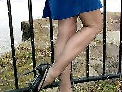 Cute Carrie is outdoors in a lovely blue dress with a pair of seamed stockings and a pair of...