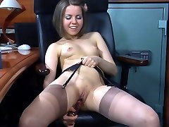 Doll-faced office babe mounts her working table for stockinged dildo toying