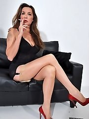 Nylon Jane dressed in lingerie and silky nylons dangles her high heel shoes and smokes in her...