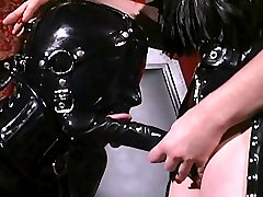 Restrained slave in skin tight latex suit sucks big strapon cock