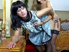 Sissified guy in a dark wig switches the roles with a strapon-armed female