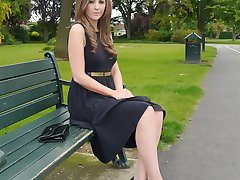 Sexy brunette Debbie takes a stroll into the park in a pretty dress and gorgeous matching black...