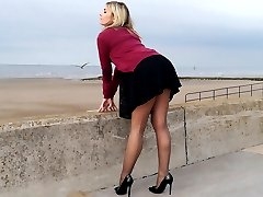 Gorgeous leggy blonde Naomi teases outdoors in a cute black summer dress, sexy nylon stockings and tall black stiletto heels! Enjoy the shoe fetish view