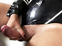 Tgirl in sexy black latex strokes her cock for your pleasure