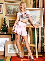 Vivacious artist stroking her seductive pantyhose clad feet with a brush