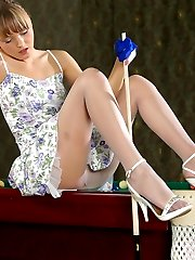 Pretty babe with yummy feet posing in sheer pantyhose on the billiard table