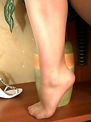 Curly babe giving a glimpse of her pedicured feet in slight sheen pantyhose