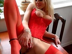 Smoking hot blonde posing in her sexy red lingerie and lets her big boobs pop out of her corset
