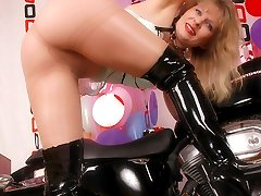 Angel in shiny pantyhose and boots on a bike