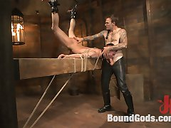 Arms bound high above his head, Chris Harder, now Slave 401, struggles to stand at attention in...
