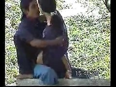 Young Latin couple pleasing each other on the bench in public park