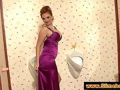 Busty redhead has fun at the gloryhole