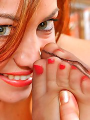 Redhead chick undressing slowly and getting nasty with her feet in tan hose