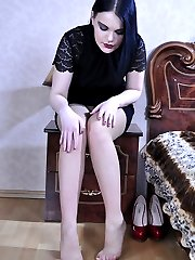 Teasing raven-head slides out of her red pumps to boast her nylon clad feet