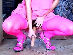 Ponytailed sweetie in pink nylons matching her dress plays with a sex toy