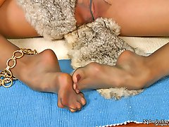 Redhead babe in silky pantyhose pampering her well-maintained feet with fur